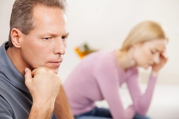 Depressed couple. Side view of depressed mature man holding hand on chin while sad woman sitting on background