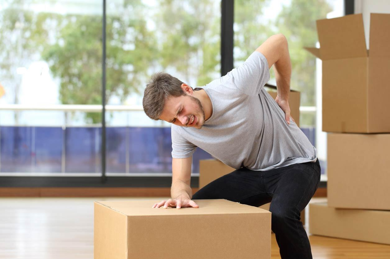 man hurting back while lifting boxes at work