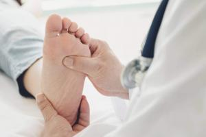 having foot examined by a doctor